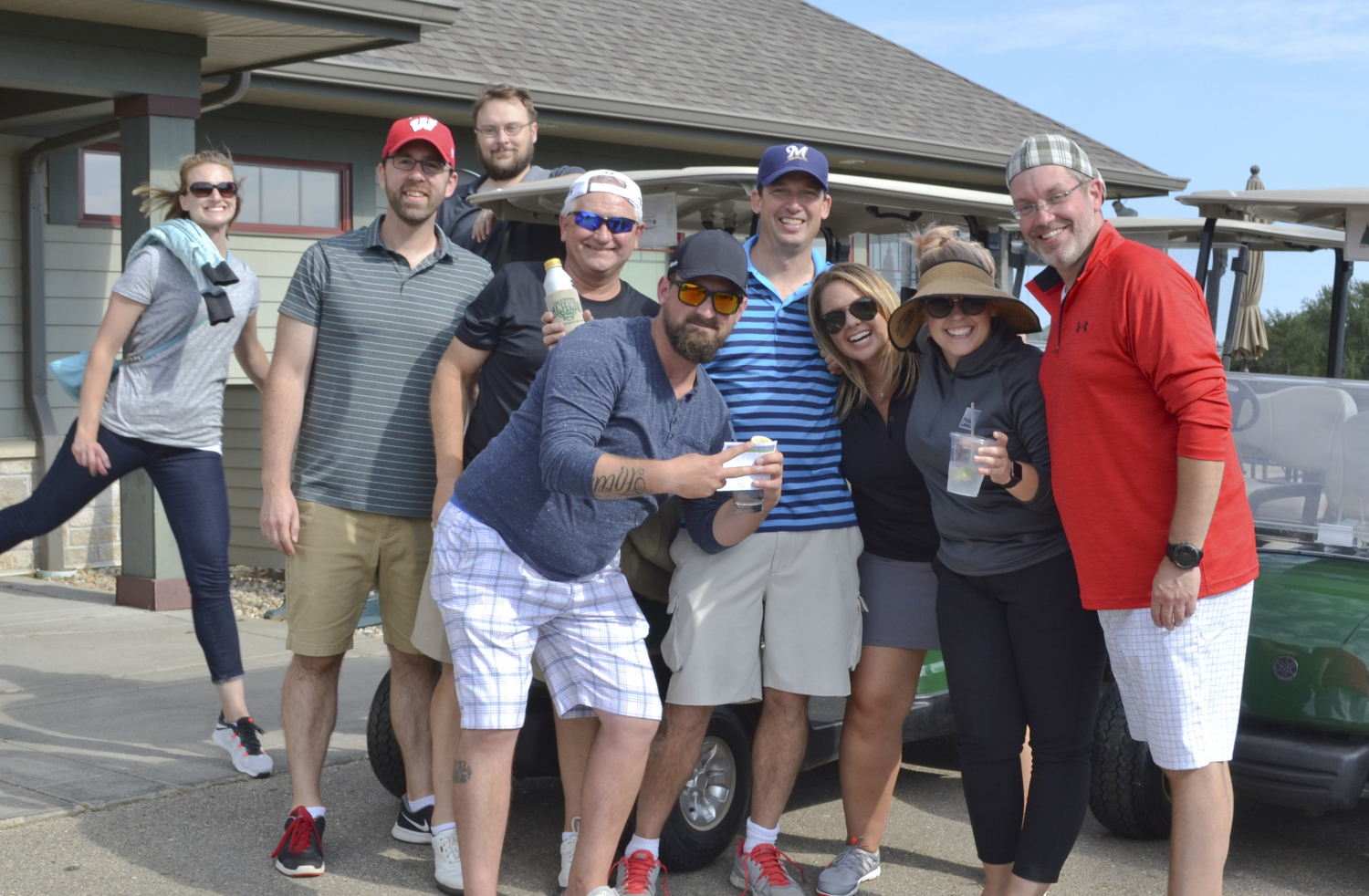 Group staff photo of 9 people smiling together at a golf clubhouse.
