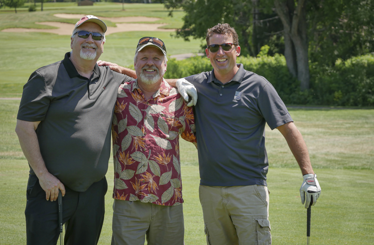 Three staff members smiling together on golf course.