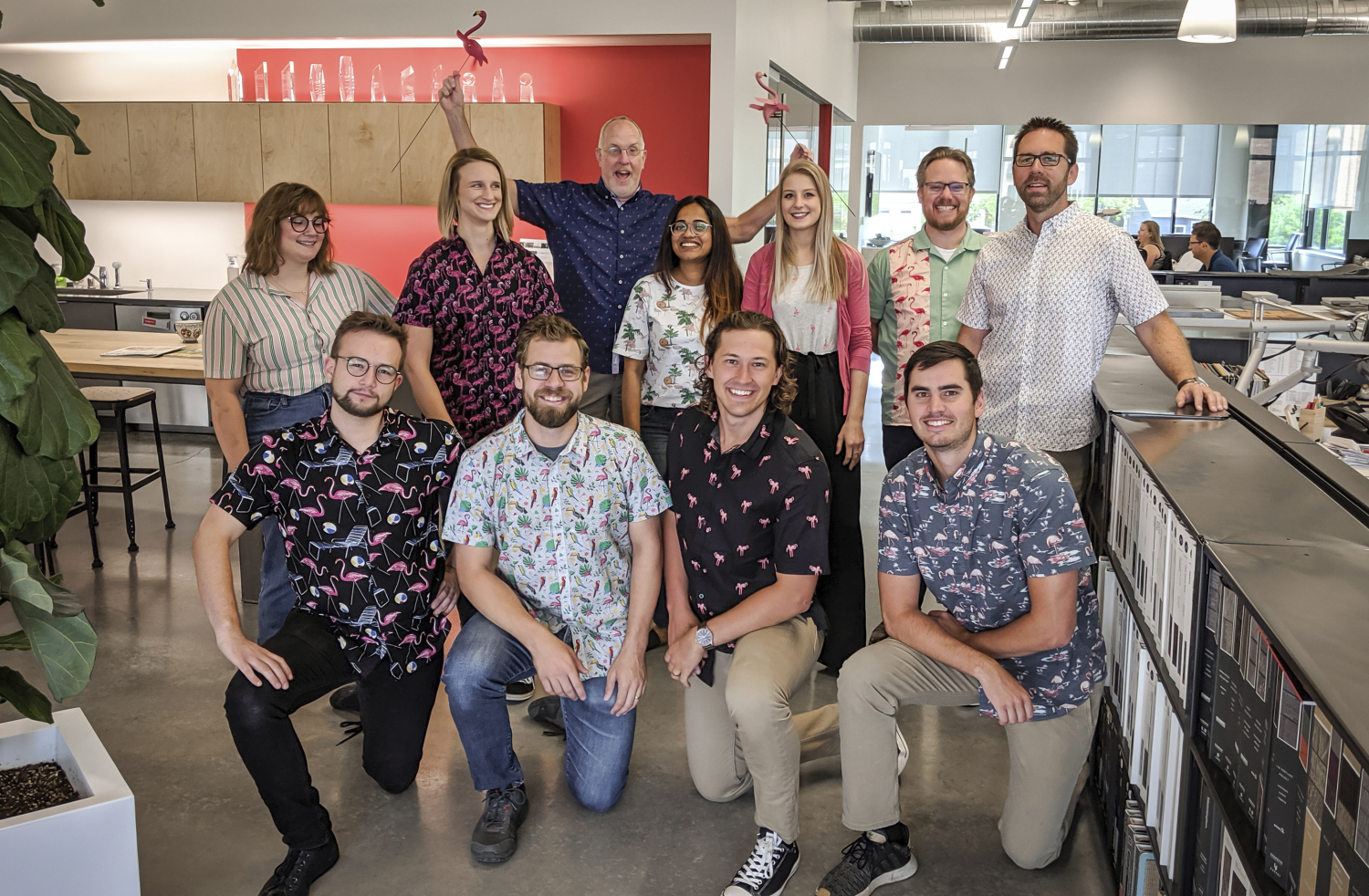 Staff group photo wearing flamingo-themed apparel. One staff member holds up two law flamingos.