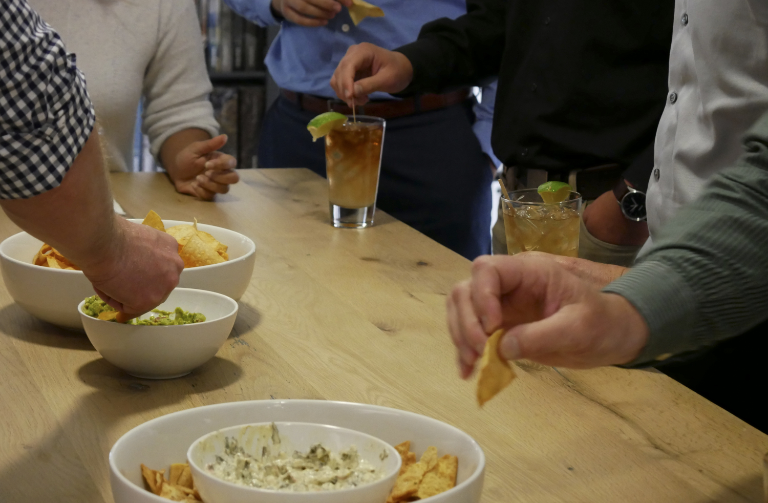 Detail shot of bowls of chips, guacamole, and dip; people standing around table eating and drinking cocktails.